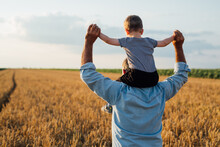 Farmer Holding His Grandson Standing In Wheat Field