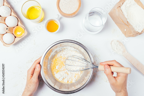 Female hands whisk flour and eggs in metal bowl to cook dough for homemade bread Poster Mural XXL