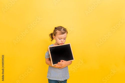 A sad little girl holds a slate on a yellow isolated background with space for t Wallpaper Mural