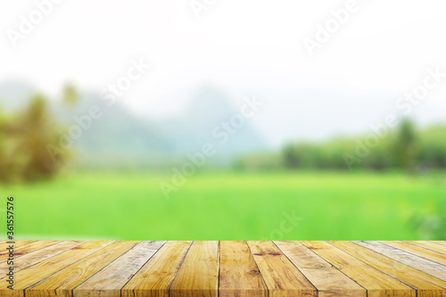 Shelf of Brown wood plank board with blurred green rice field farm with mountain and hut nature background.