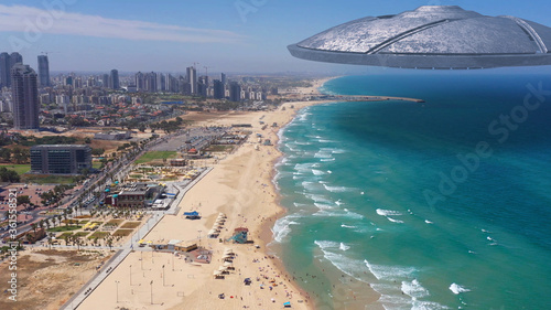 Fototapeta Alien ufo Saucers spacecraft flying over sea and coastline of large city