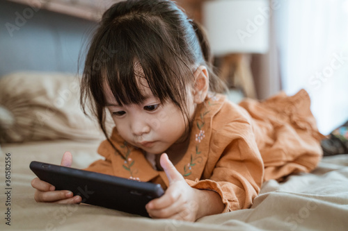Fotografie, Obraz little girl laughed happily when holding a phone to see the child's video