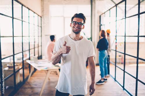 Half-length portrait of skilled team member in eyewear showing ok gesture while Fototapet