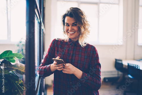 Fotografie, Tablou Half-length portrait of smiling female student using smartphone for sending chat