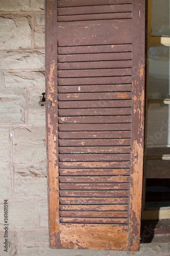 Photo Weathered and peeling shutter for window on house