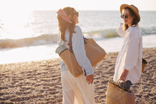 Two Young Beautiful Women Female Friends Going To Have Summer Picnic On A Beach At Sunset.