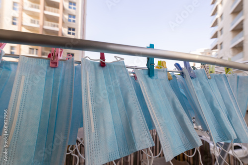 Fototapety, obrazy: Blue disposable surgical mask washed and hanging on a drying rack. Concept of shortage of personal protection equipment (PPE). Concept of re usability and recycling during crisis times.