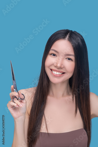 Photo Smiling woman thinking about making anew haircut