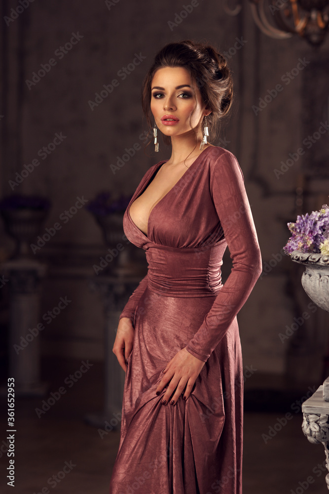 Fototapeta Young beautiful lady in evening dress posing in dark interior and looking at you