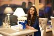 Beautiful elegant lady enjoying glass of champagne and celebrating holiday in restaurant