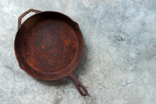 Old Rusty Round Cast Iron Frying Pan On   Grey Cement Background, View From Above