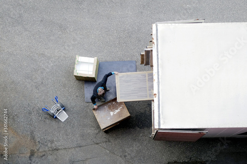 Mover unload furniture and boxes from moving truck Wallpaper Mural