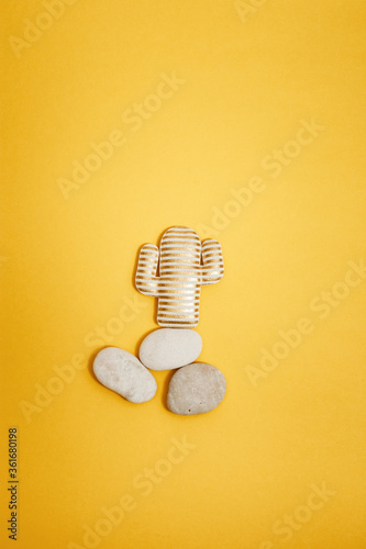 Valokuva Summer composition with soft toy, golden striped cactus on round stones on yellow paper background