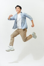 Energetic Happy Young Asian Man In Casual Clothes Jumping, Studio Shot Isolated