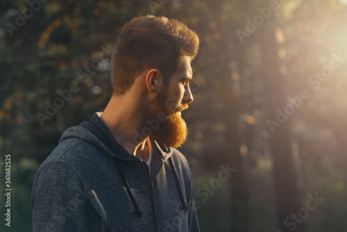 Fototapeta Profile young handsome serious bearded man. Hipster walking in a park. Portrait of man looking at sunrise in the forest Copy free space for advertising obraz
