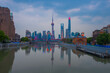 Sunset view of Waibaidu Bridge and Lujiazui, the skyline and landmark in Shanghai, China, with reflection in front.