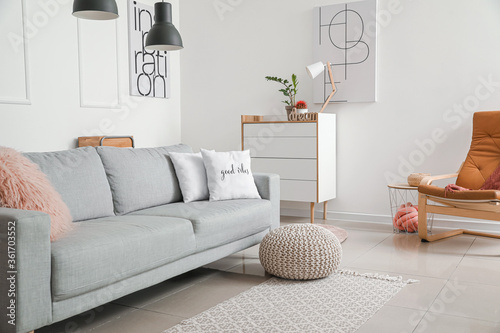 Stylish sofa with chest of drawers in living room