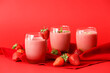 canvas print picture - Glasses of tasty strawberry smoothie on color background