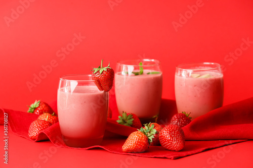 Glasses of tasty strawberry smoothie on color background
