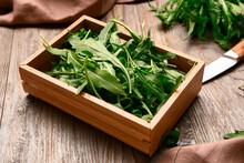 Box With Fresh Arugula On Wood...