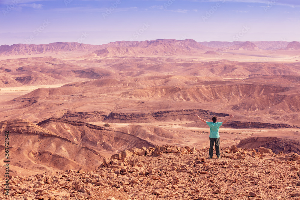 Fototapeta A man with arms in the air stands on the edge of a cliff and looks at a desert landscape