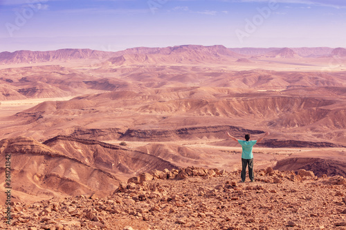 Fototapeta A man with arms in the air stands on the edge of a cliff and looks at a desert landscape obraz