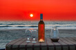 canvas print picture - Bottle of rose wine and glasses on the table at Sunset in beach cafe, GOA, India