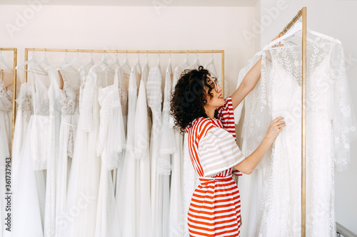 Foto Consultant at a wedding showroom showing new bridal dress collection