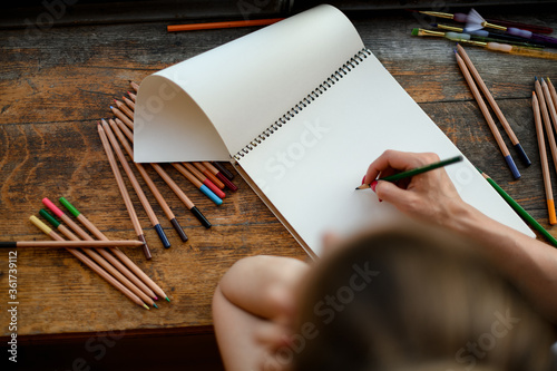 Top view on the hand of woman who draws with colored pencils in sketchbook Canvas Print