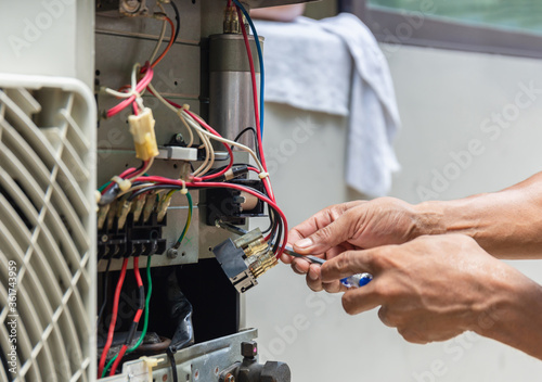 Obraz na plátně Close up of Air Conditioning Repair, repairman installing magnetic contactor and