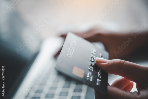 Fotografering Close up hands holding credit card, typing on the keyboard of laptop, online sho