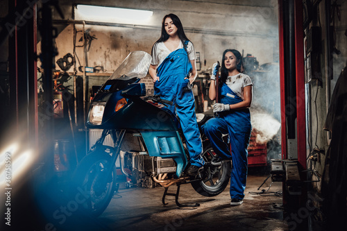 Two hot brunette women in blue overalls posing next to a sportbike in authentic workshop garage