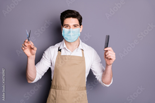Portrait of his he attractive guy barber wearing safety mask holding in hands scissors comb social distance stop infection mers cov preventive measures isolated grey color background