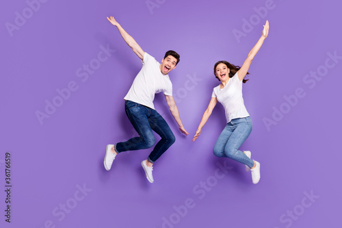 Full length photo of cheerful married couple man woman jump enjoy leisure free time rest wear casual style clothes sneakers isolated over violet color background