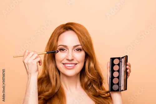 Close-up portrait of her she nice-looking attractive lovely sweet fascinating cheerful mature wavy-haired lady applying modern cool shine tint glitter foundation isolated over beige pastel background