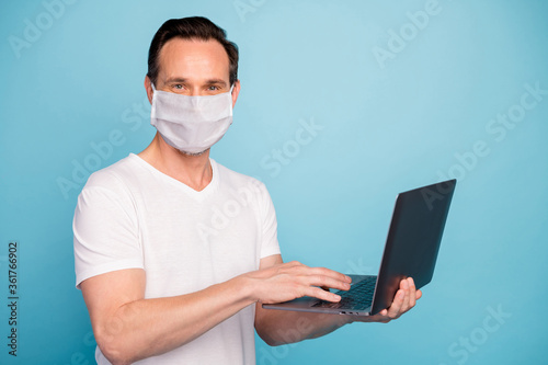 Portrait of his he nice skilled guy wearing safety mask working remotely on laptop watch video lesson stop flu grippe disease case healthcare isolated bright vivid shine vibrant blue color background