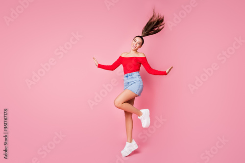 Full length profile photo of pretty funky lady rejoicing students disco party jumping excited wear red open shoulders shirt mini denim skirt shoes isolated pastel pink color background