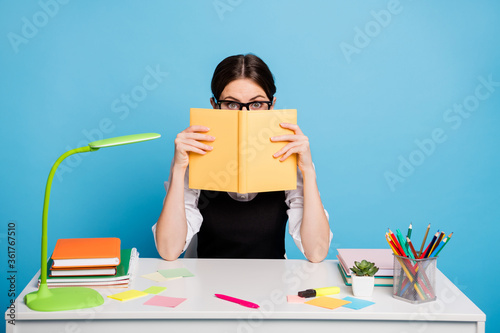 Photo of astonished high school girl sit table close cover face copybook hide herself from graduate exam preparation wear black white stylish overall uniform isolated blue color background