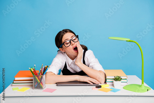 Photo of tired bored high school girl sit desk yawn hand mouth sleep lesson lecture wear white black uniform overall isolated over blue color background