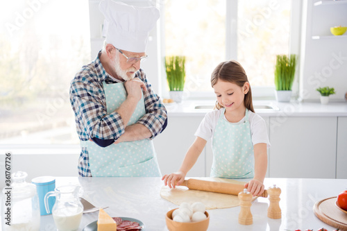 Photo of little girl granddaughter passing examination aged chef grandpa looking attentively forming dough rolling pin baking cookies weekend home kitchen indoors