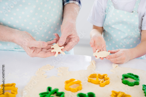 Cropped close-up view of nice hands granddad grandchild preparing cooking cookies sweet snack using cutter animal shape form figure help assistance in modern light white interior kitchen house