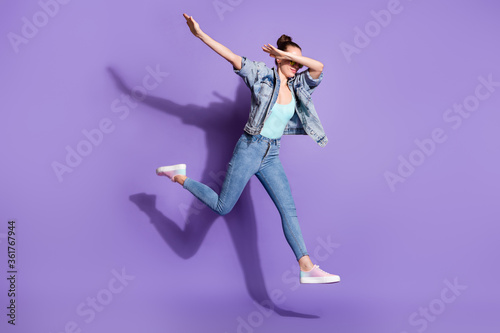 Full size photo of pretty youth girl jump dance hip-hop dab close cover face arms wear denim jacket singlet glasses sunglasses isolated over purple color background