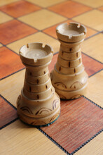 Two White Rooks Figures Stands On A Chessboard. Wood Game Chessboard Background.