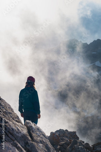 Persona de espaldas asomada al precipicio desde una cumbre con luces de la niebl Canvas Print