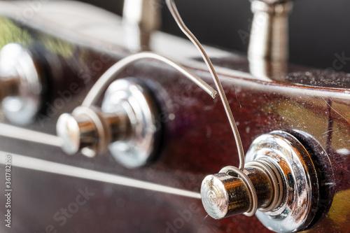 Obraz Nawinieta struna na klucz. Gitara akustyczna. Zdjecie makro klucza gitarowego - fototapety do salonu