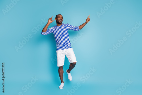 Fototapeta Full length photo of cheerful energetic afro american guy enjoy disco club music dance close eyes feel pleasure wear nautical vest gumshoes isolated over blue color background obraz