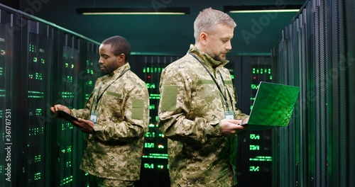 Mixed-races male military co-workers operating with data in server center and checking information with tablet device amd laptop computer. African American and Caucasian men working with servers.