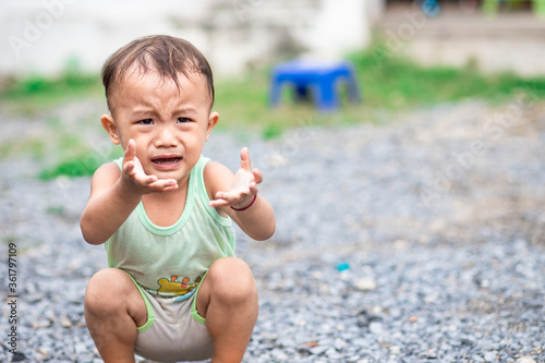 Little naughty Asian child sitting and crying Fototapet