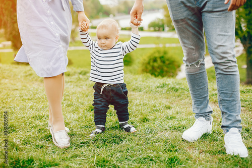 Obraz A young and beautiful blonde mother in a blue dress, along with her handsome man dressed in a white jacket, walks with her little son in the summer solar park - fototapety do salonu