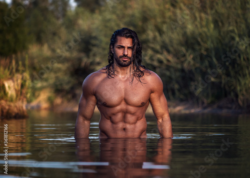Fotografía Long haired bearded muscular man shirtless stands waist deep in the water